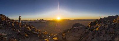 Afrika, namibia, hardap, hammerstein, kulala wilderness reserve, zaris mountains, woman standig at namib desert at sunset — Stockfoto