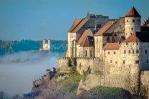 Буря, замок, утренний туман и здания на холме — стоковое фото