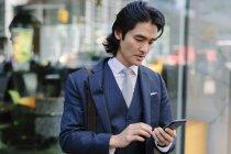Asiatischer Geschäftsmann schaut aufs Handy — Stockfoto