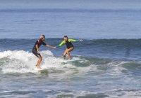 Man helping woman on surfboard in sea — Stock Photo