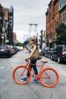 EUA, Nova Iorque, Williamsburg, mulher withg vermelho corridas ciclo atravessando a rua — Fotografia de Stock