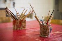 Tazza con pennelli e strumenti sul tavolo — Foto stock