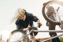 Vélo Bmx réparation de jeune femme — Photo de stock