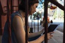 Mujer sentada en escaleras con tableta digital - foto de stock