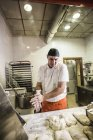 Experienced pizza baker preparing dough for pizza in his bake shop — Stock Photo