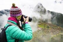 Peru, Machu Picchu region, Travelling woman taking picture of Machu Picchu Citadel — Stock Photo