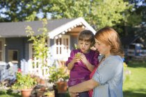 Mother holding daughter with apple in garden — Stock Photo