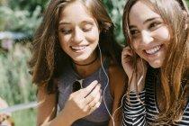 Два счастливых друга делятся наушниками — стоковое фото