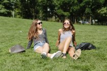Two young women relaxing in a park — Stock Photo