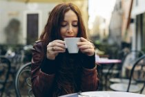 Woman having a coffee outdoors in a little bar — Stock Photo
