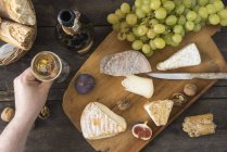 Cheese platter with camembert, walnut cheese, gorgonzola, taleggio and male hand holding glass of champagne — Stock Photo