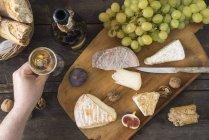 С сыром камамбер, сыр орех, горгонзола, Таледжио и мужской рукой, держащей стакан шампанского — стоковое фото