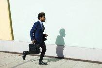 Giovane uomo d'affari con valigetta in esecuzione sul marciapiede — Foto stock