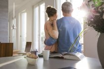Couple looking out of window  in kitchen — Stock Photo