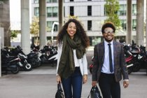 Two smiling young business people walking in city — Stock Photo