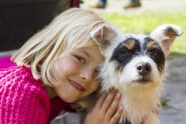 Girl hugging Jack Russel Terrier — Stock Photo