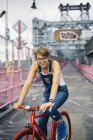 USA, New York City, Williamsburg,  portrait of blond woman with red racing cycle on Williamsburg Bridge — Stock Photo