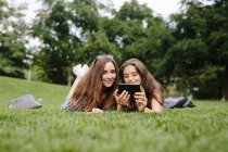Two friends in a park looking at cell phone — Stock Photo
