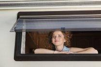 Porträt einer lächelnden jungen Frau, die durch das Fenster ihres Wohnwagens blickt — Stockfoto