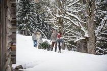 Due coppie e due bambini trasporto dell'albero di Natale nella foresta di inverno — Foto stock