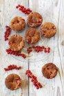 Grosellas rojas y magdalenas en placa de vidrio y madera - foto de stock