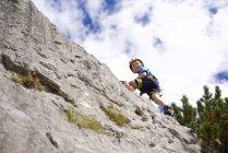 Vue faible angle de petit garçon, le rocher d'escalade dans la journée — Photo de stock