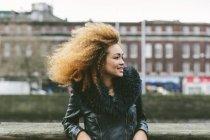 Усміхаючись жінка з афро волосся, дивлячись сторону — стокове фото