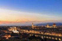 Italia, Toscana, Florencia, paisaje urbano, vista del río Arno, Ponte Vecchio y el Palazzo Vecchio en la noche - foto de stock