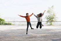 Portrait of happy young couple jumping in the air on view terrace — Stock Photo