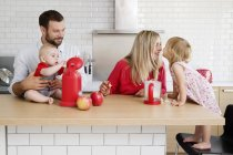 Family of four in the kitchen preparing apple sauce together — Stock Photo