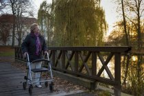 Senior woman with wheeled walker walking on footbridge in the evening — Stock Photo