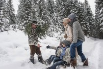 Man walking with Christmas tree and family together in winter forest — Stock Photo