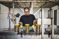 Man in factory at conveyor belt with filled olive glasses — Stock Photo
