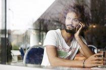 Портрет задумчивого мужчины, сидящего в кафе и звонящего со смартфоном — стоковое фото
