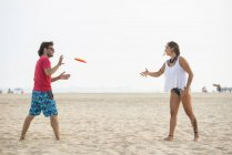 Espanha, Cádiz, El Puerto de Santa Maria, Casal jogando frisbee na praia — Fotografia de Stock