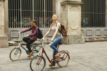 Two young women riding bicycle in the city — Stock Photo
