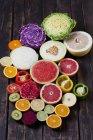 Hälften verschiedener Gemüse- und Obstsorten auf dunklem Holz — Stockfoto