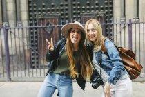 Испания, Барселона, две веселые девушки перед входом. — стоковое фото