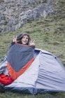 España, Picos de Europa, hombre feliz dentro de una bolsa de dormir - foto de stock