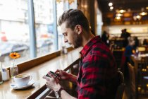 Man in a coffee shop looking at cell phone — Stock Photo