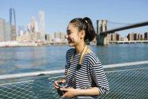 USA, New York City, jeune femme souriante avec caméra — Photo de stock