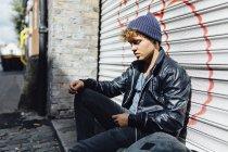 Молодой человек опирается на рольставни — стоковое фото