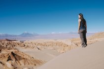 Chile, Atacama Desert, woman standing on a dune looking at view — Stock Photo