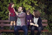Сміючись батьки сидять на лавці лоскоту їх маленької дочки — стокове фото