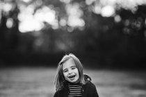 Портрет сміється дівчинка на відкритому повітрі, дерев на тлі — стокове фото