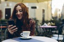 Donna con cellulare che prende un caffè all'aperto in un piccolo bar — Foto stock