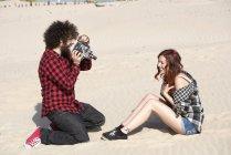 Giovane uomo riprese la sua ragazza sulla spiaggia — Foto stock