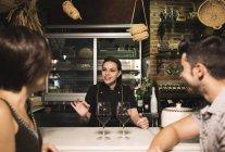 Lächelnde Kellnerin und Paar mit Rotweingläser in Bar — Stockfoto