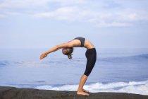 Indonesien, Bali, Frau praktizieren Yoga an der Küste — Stockfoto