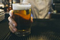 Cropped image of Waitress serving fresh beer — Stock Photo